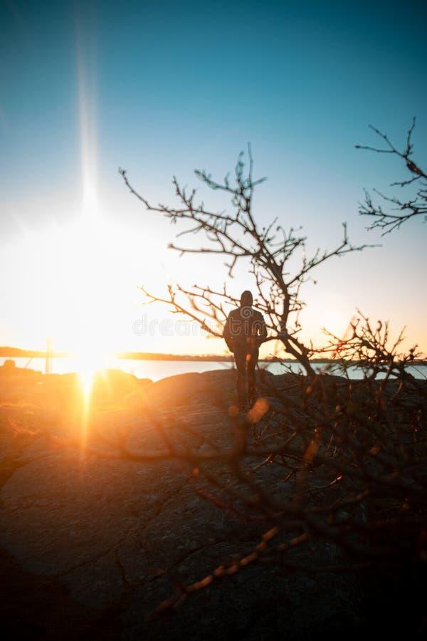 Persona che cammina verso il tramonto immagini stock