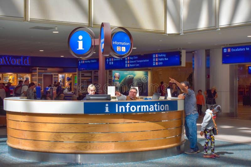 Persona che dà le indicazioni ad un passeggero nel centro d'informazione ad Orlando International Airport immagine stock