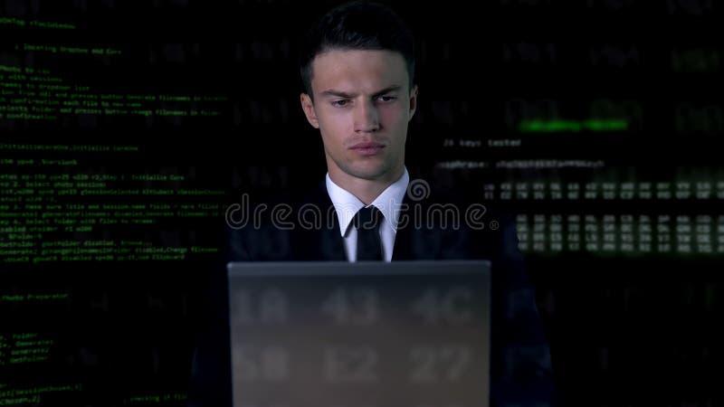 Persona che digita in costume sul portatile, codice software in background, hack password immagini stock libere da diritti