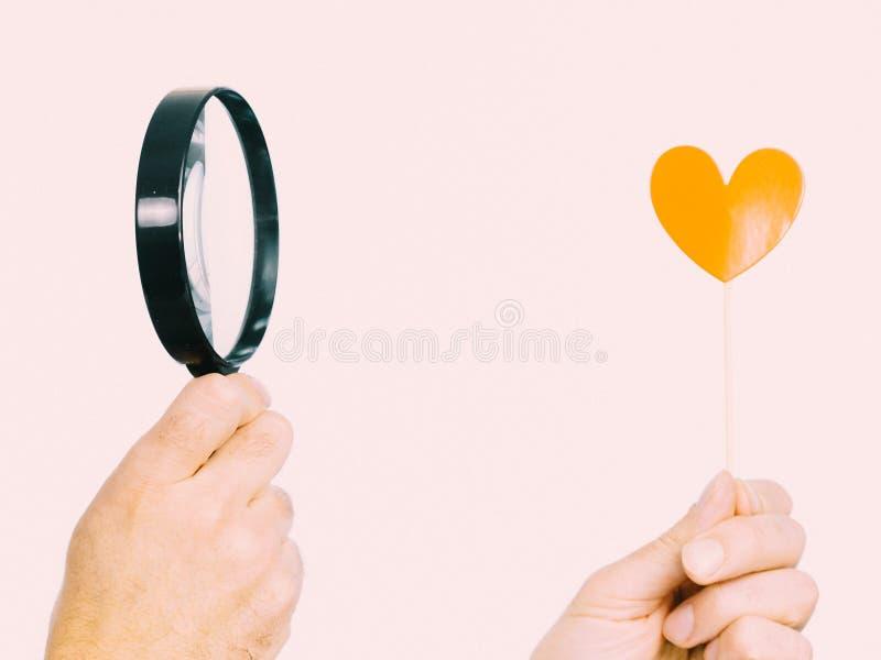 Persona che esamina cuore tramite la lente d'ingrandimento immagine stock libera da diritti