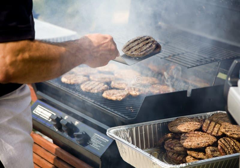 Persona che lancia gli hamburger durante il BBQ fotografia stock libera da diritti