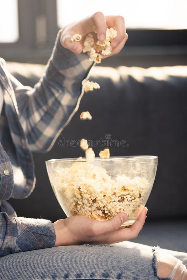Persona che mangia popcorn dalla ciotola di vetro immagine stock libera da diritti