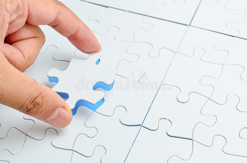 Persona che misura l'ultimo pezzo di puzzle immagine stock
