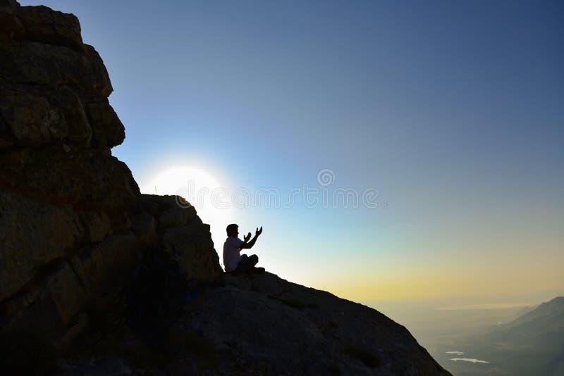 Persona che prega sul fianco di una montagna fotografie stock