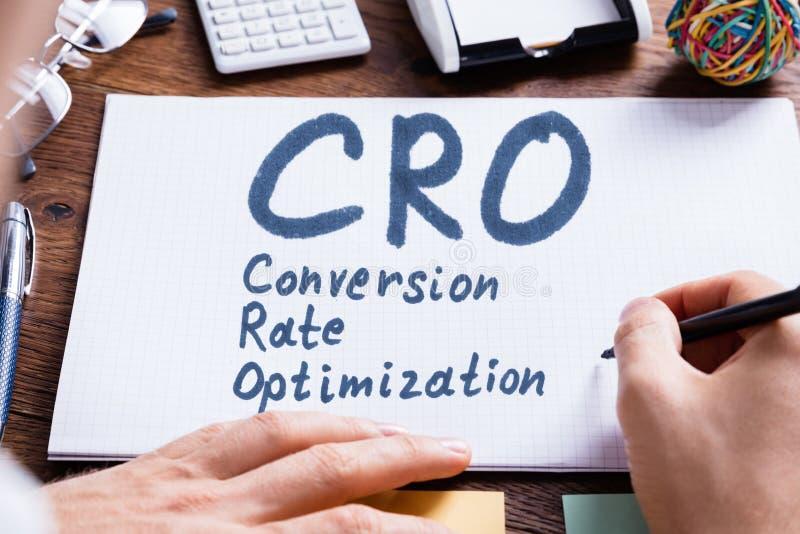Persona che scrive conversione Rate Optimization On Book immagine stock libera da diritti