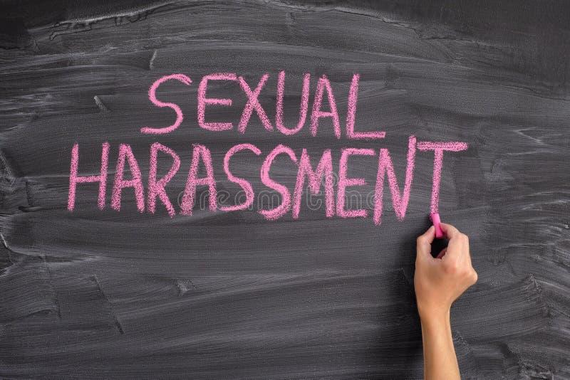 Persona che scrive la molestia sessuale di parole su una lavagna fotografie stock