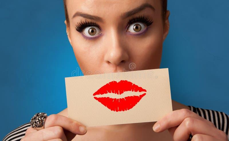 Persona che sorride con una carta davanti alla sua bocca fotografie stock libere da diritti