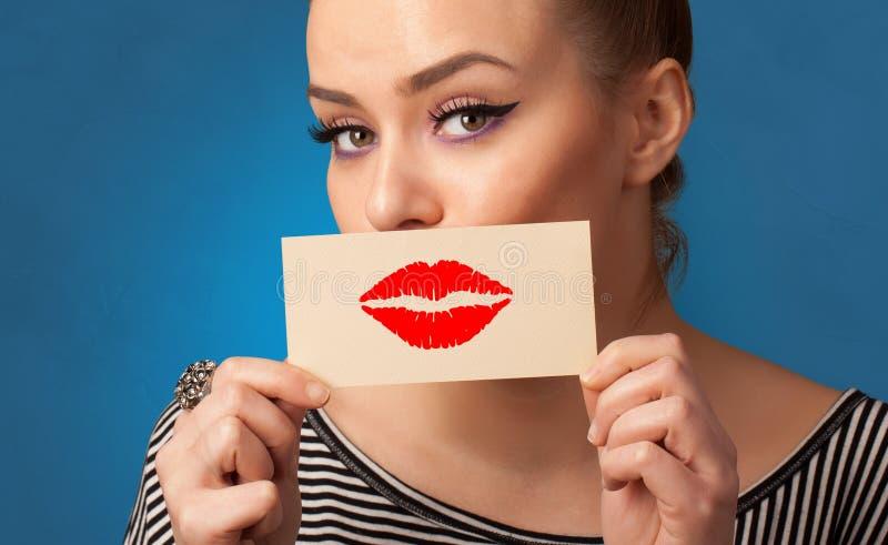 Persona che sorride con una carta davanti alla sua bocca immagini stock