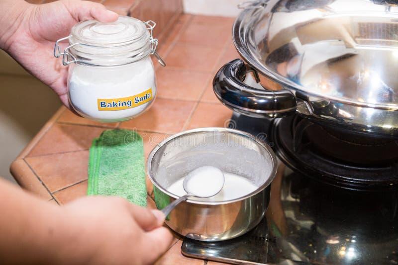 Persona che tiene il bicarbonato di sodio misto della cucchiaiata, efficace cle naturale fotografie stock libere da diritti