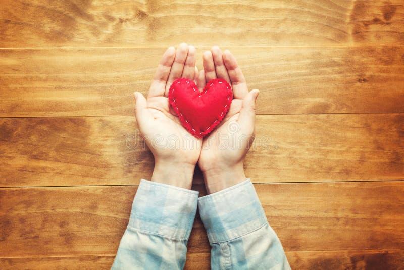 Persona che tiene un cuore rosso fatto a mano fotografia stock libera da diritti