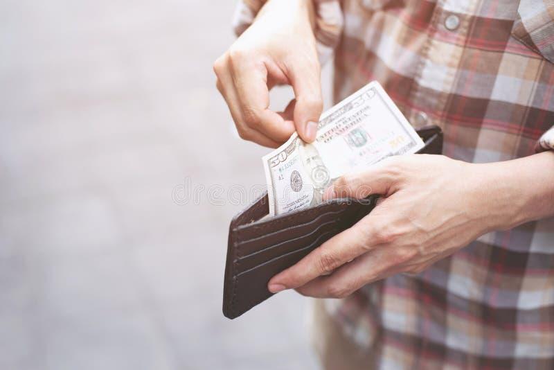 Persona che tiene un portafoglio nelle mani dei soldi della presa dell'uomo fotografie stock