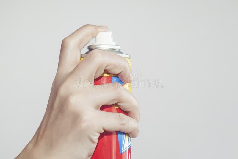 Persona che usando uno spruzzo per l'uccisione le zanzare, aerosol contro le zanzare e delle mosche Spruzzo di controllo o dell'u fotografia stock