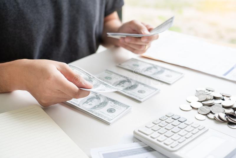 Persona che utilizza il calcolo e calcola l'incasso fatture nei costi di pagamento spese di casa con nota cartacea, gestione cont immagine stock