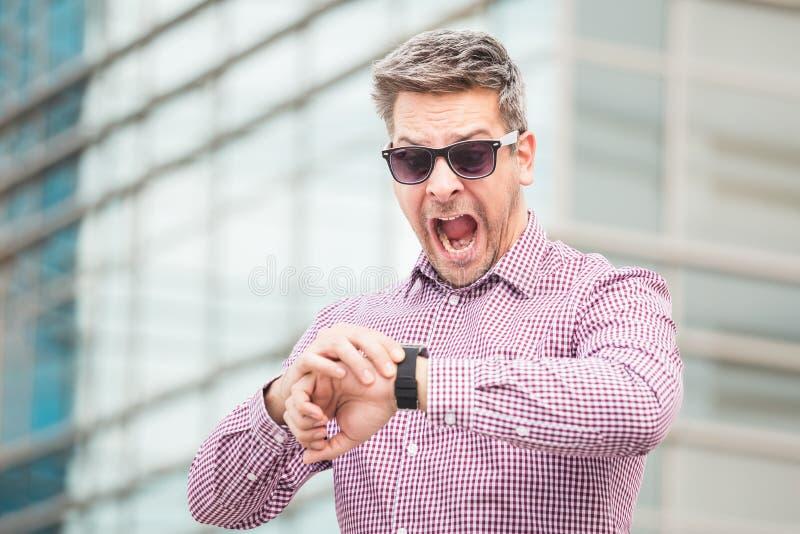 Persona chocada del negocio mientras que comprueba tiempo en su reloj al aire libre fotos de archivo