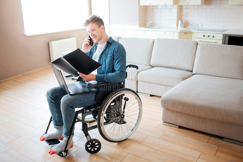 Persona con necesidades especiales en silla de ruedas Estudiante joven que mira el libro abierto y que habla en el tel?fono Solam foto de archivo libre de regalías