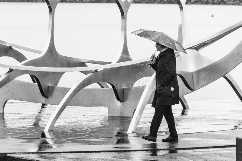 Persona con umbrela cerca de Solfarid - viajero de Sun en Reykjavik fotografía de archivo