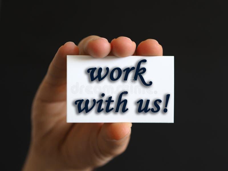 Persona con un trabajo con nosotros tarjeta a disposición o papel de nota foto de archivo