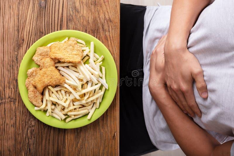 Persona de Fried Food In Front Of que tiene dolor de est?mago imagen de archivo libre de regalías