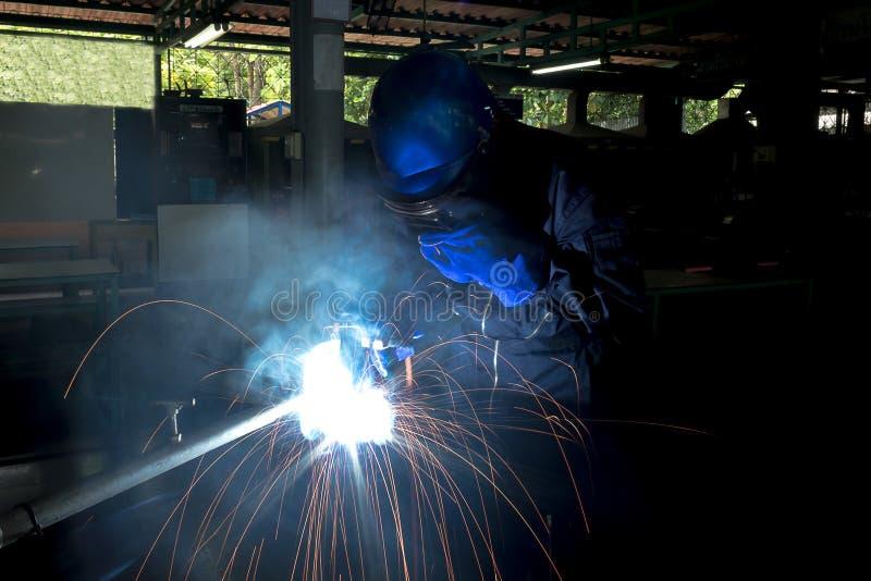 Persona de funcionamiento sobre el acero del soldador usando la soldadura eléctrica imagenes de archivo