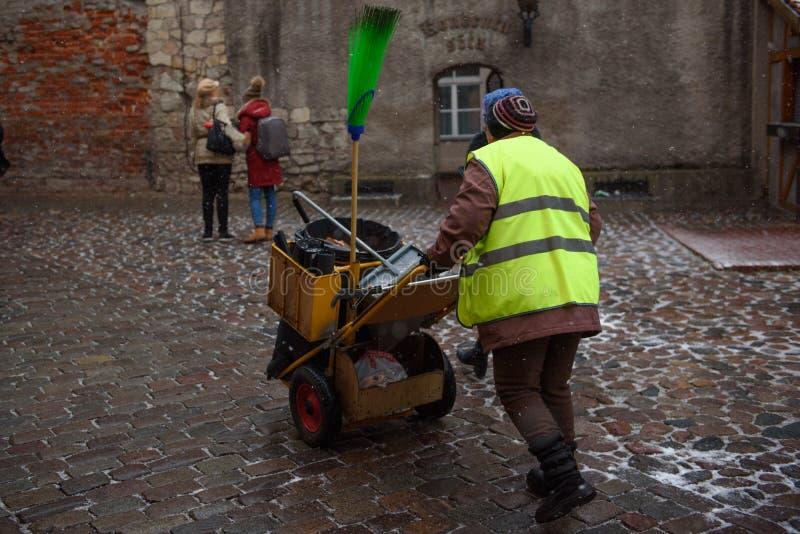 Persona de la limpieza de la calle que camina con las ruedas en la calle resbaladiza imagenes de archivo