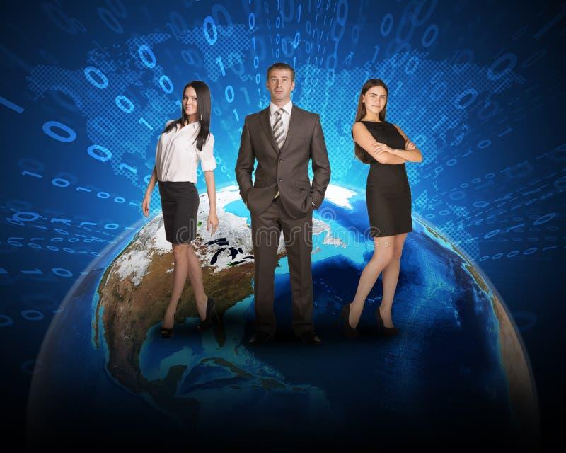 Persona de tres negocios que se coloca en superficie de tierra imagenes de archivo