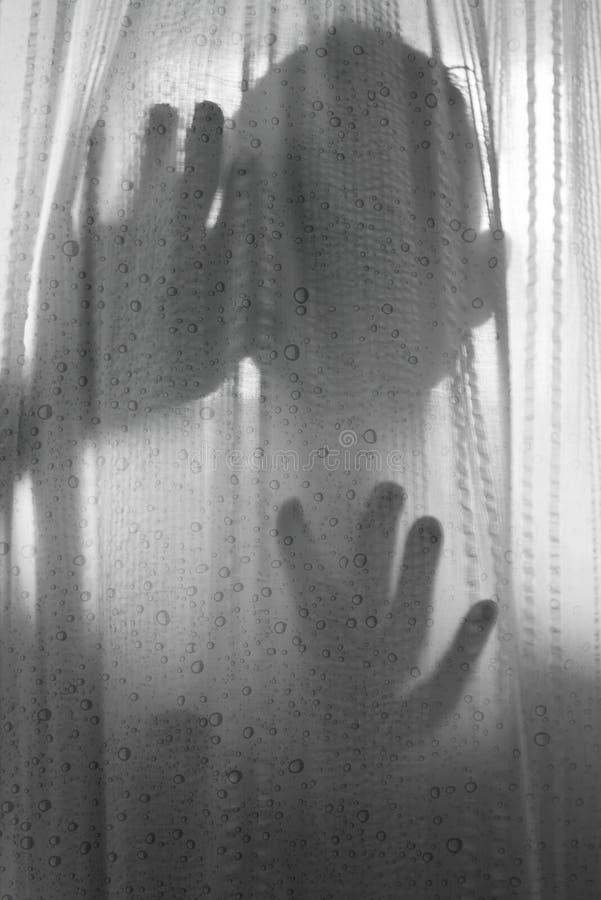 Persona del horror detrás de la cortina de ducha en blanco y negro imagen de archivo
