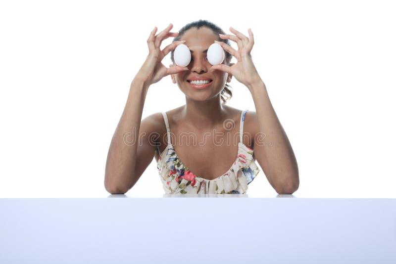 Persona del mulato que come el huevo dos delante del ojo imagenes de archivo
