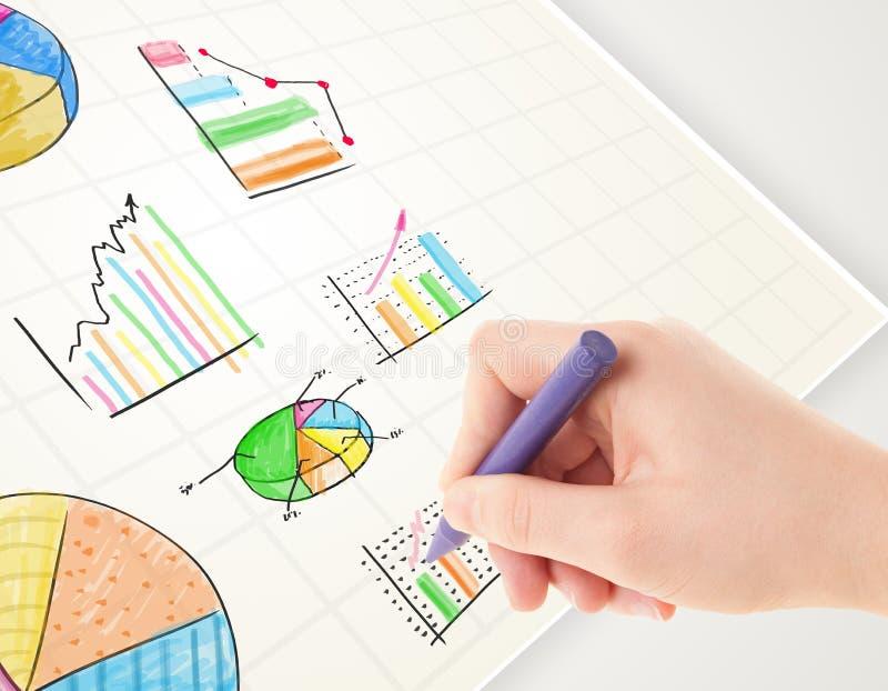 Persona del negocio que dibuja gráficos e iconos coloridos en el papel foto de archivo libre de regalías