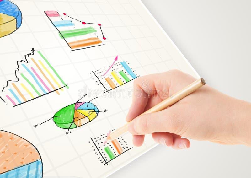 Persona del negocio que dibuja gráficos e iconos coloridos en el papel imagen de archivo