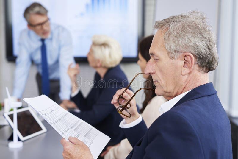 Persona del negocio que lee documentos importantes imagen de archivo libre de regalías