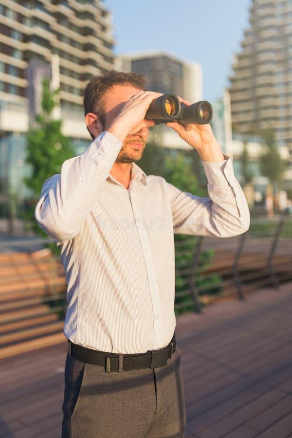 Persona del negocio que mira a través de los prismáticos delante de edificios del negocio imagen de archivo