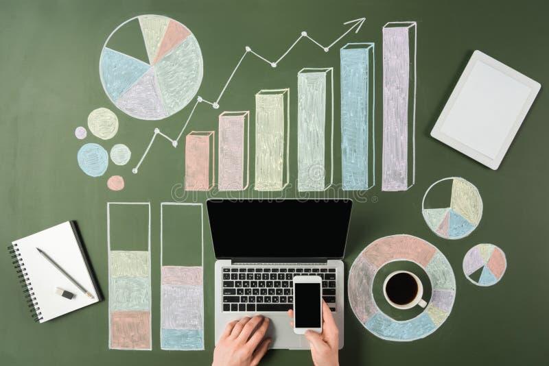 Persona del negocio que usa los dispositivos digitales en el lugar de trabajo con los gráficos coloridos imagen de archivo libre de regalías