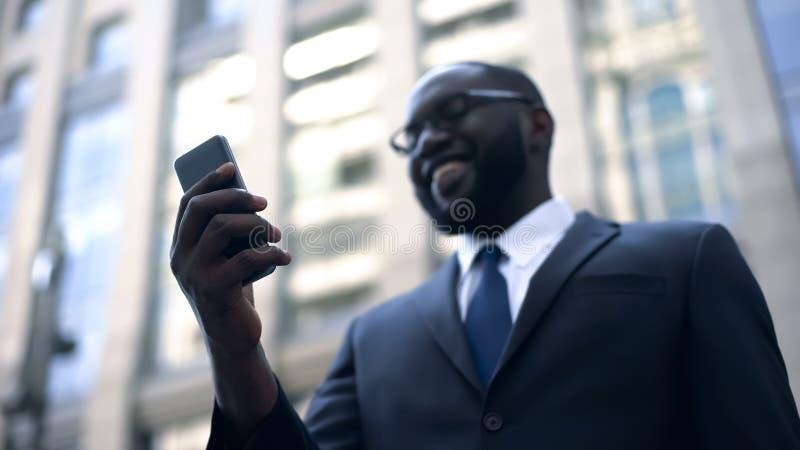 Persona del negocio satisfecha con el trabajo del uso en el smartphone, actividades bancarias en línea fotografía de archivo