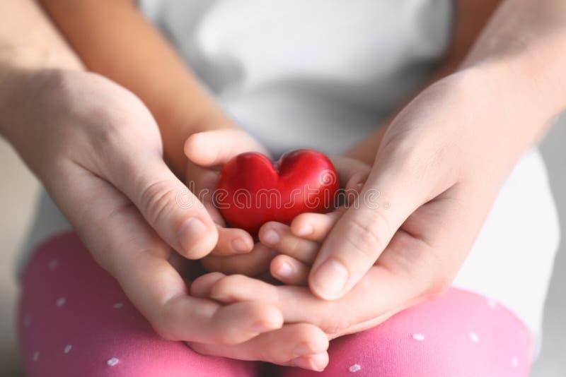 Persona dell'adulto e del bambino che tiene piccolo cuore rosso fotografie stock