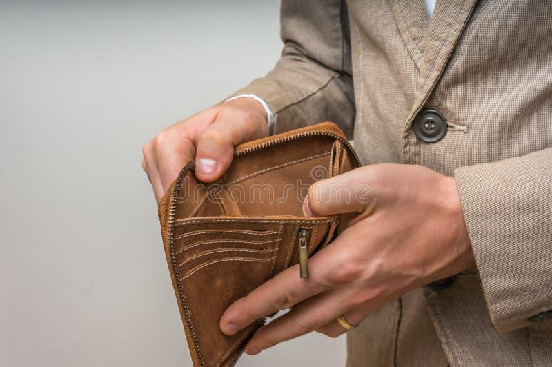 Persona dell'uomo d'affari che tiene un portafoglio vuoto, nessun soldi fotografie stock libere da diritti