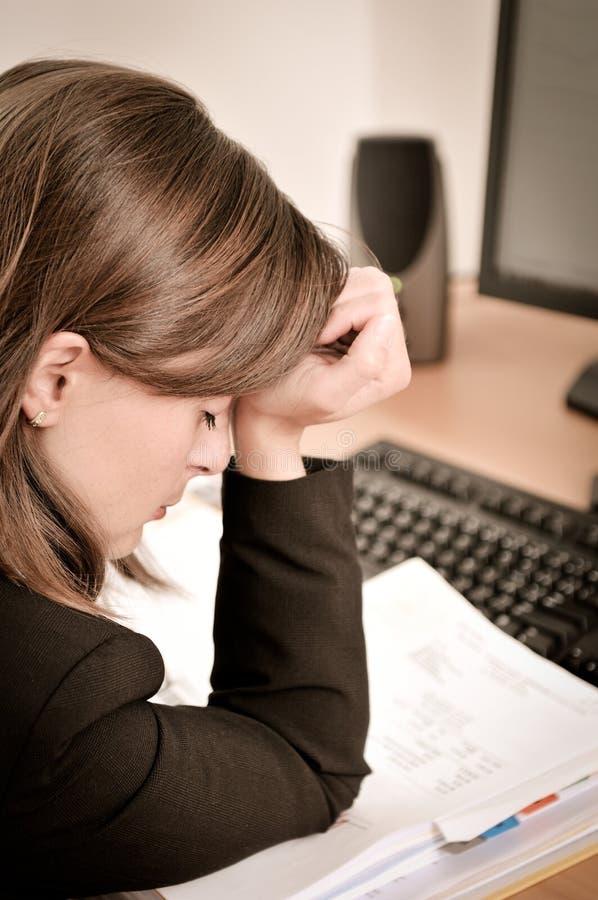 Persona deprimida del asunto con dolor de cabeza en trabajo fotografía de archivo libre de regalías