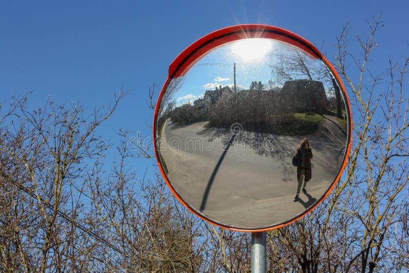 Persona desconocida que toma la imagen con una cámara de la reflexión en el espejo de la seguridad en el borde de la carretera imagen de archivo libre de regalías