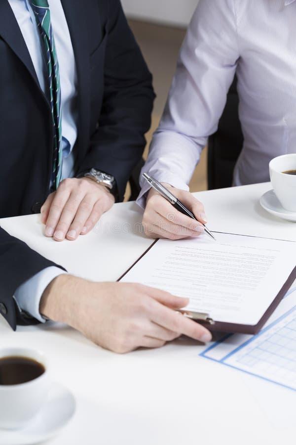 Persona di affari che firma documento importante immagine stock libera da diritti