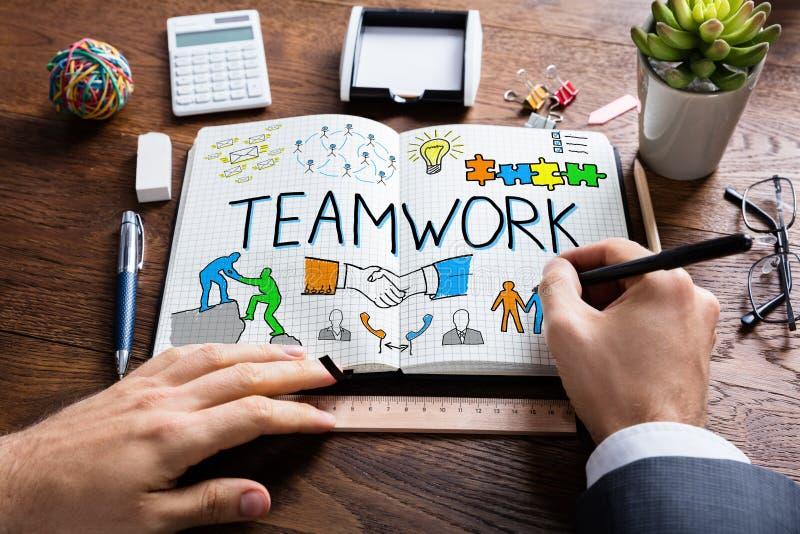 Persona di affari Drawing Teamwork Concept sul taccuino fotografie stock