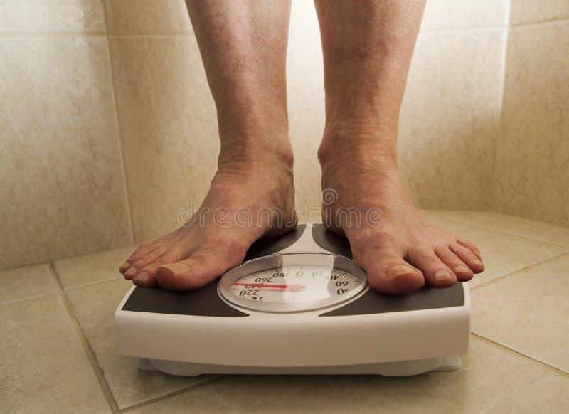 Persona di peso eccessivo sulla scala fotografia stock