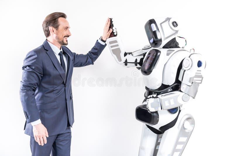 Persona di sesso maschile allegra che fa gli amici con il cyborg fotografie stock