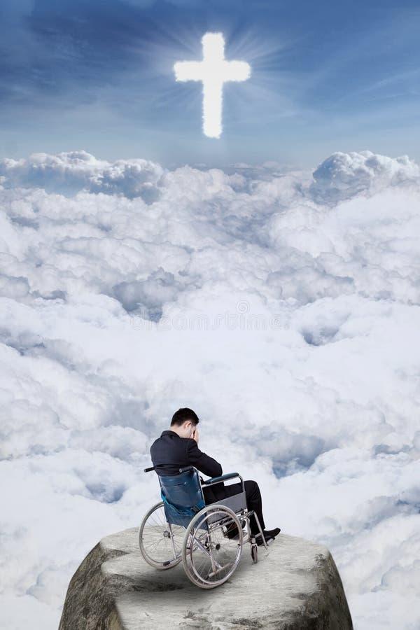 Persona discapacitada que se sienta en la silla de ruedas en el acantilado imagenes de archivo