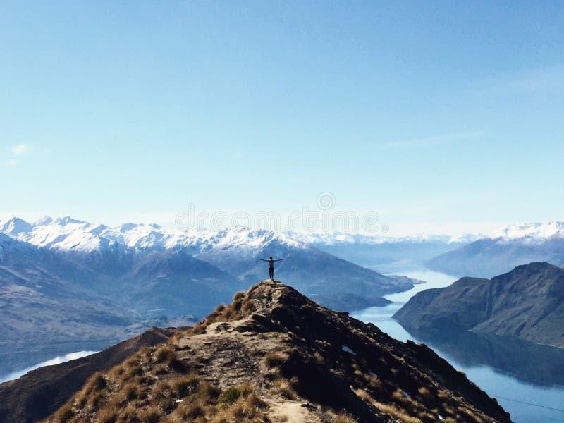 Persona en el pico de montaña que pasa por alto el lago con los brazos abiertos fotos de archivo libres de regalías