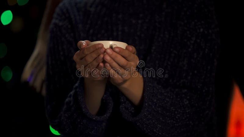 Persona en el suéter pobre que se calienta con la taza de té caliente, caridad para sin hogar y hambriento fotos de archivo libres de regalías