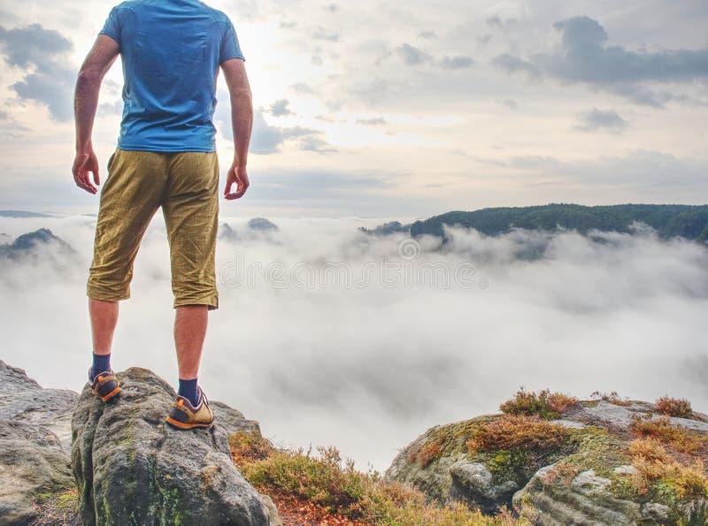 Persona en un top de montañas en una nube brumosa Opinión de la salida del sol imágenes de archivo libres de regalías