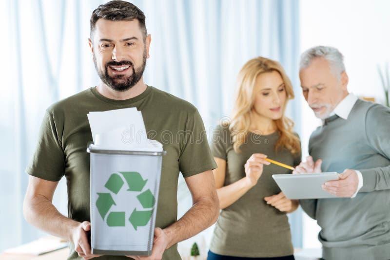 Persona entusiasta que anima a sus colegas a reciclar el papel fotografía de archivo libre de regalías