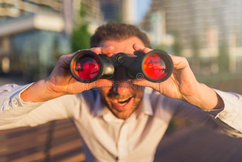 Persona feliz del negocio que mira a través de los prismáticos fotos de archivo
