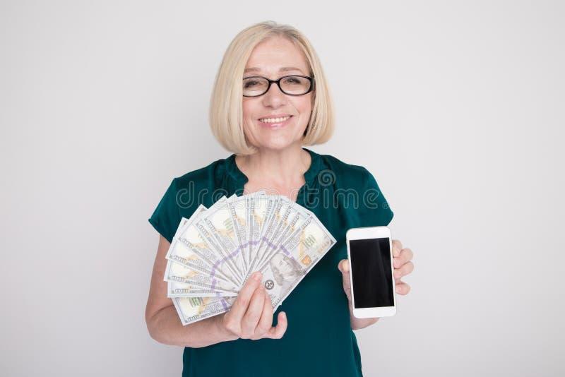 Persona femenina adulta que sostiene el dinero y el teléfono en sus manos en un estudio blanco fotos de archivo libres de regalías