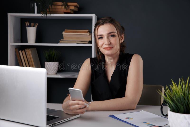 Persona femenina atractiva usando el teléfono en la oficina que se sienta en el escritorio aislado imagenes de archivo