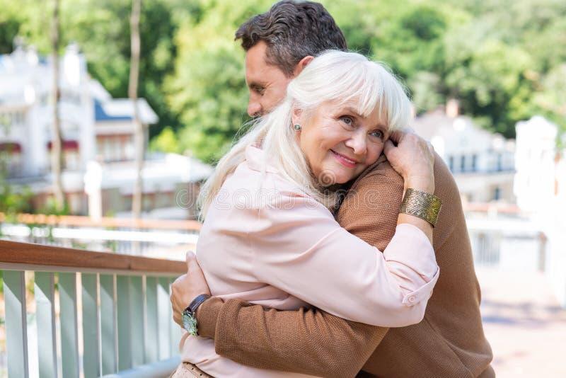 Persona femenina buena que se inclina en hombro de su hijo imagen de archivo